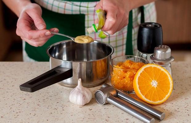 горчица в столовой ложке над сотейником на столе, рядом половинка апельсина, пресс для чеснока, солонки и апельсиновый джем в стакане