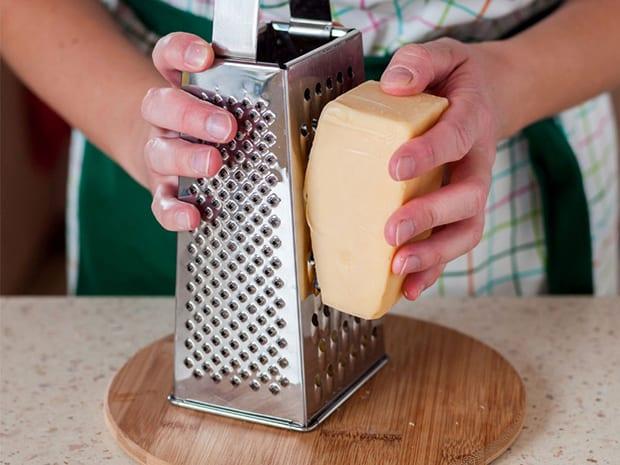 твердый сыр натирается на терке на круглой разделочной доске на столе