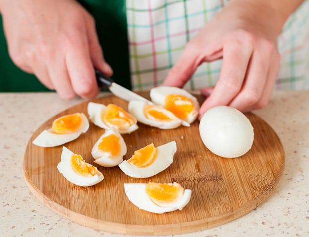 отварные яйца, нарезанные четвертинками, на разделочной доске на столе