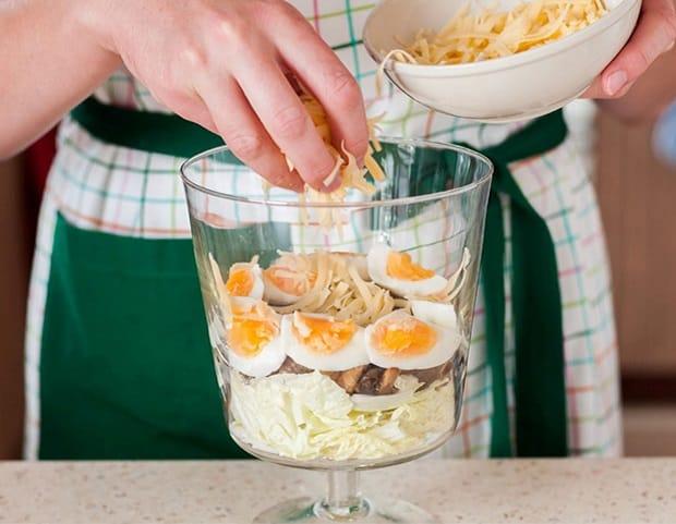 в салатницу с пекинской капустой, грибами и яйцами добавляется тертый сыр