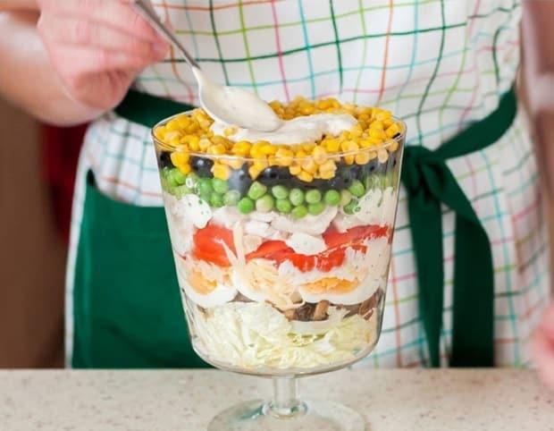 слоеный салат из шампиньонов, курицы, яиц, консервированного горошка и кукурузы в салатнице на ножке на столе