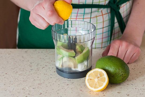 половинка лимона выдавливается в чашу блендера с нарезанным авокадо, рядом половинка лимона и целое авокадо на столе