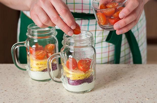 в баночки с йогуртом, красным луком и яблоками выкладываются нарезанные помидоры черри