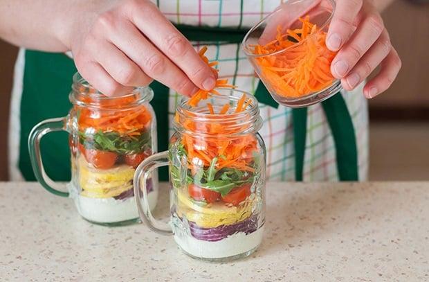 тертая морковь выкладывается в баночки с йогуртом, нарезанными луком, яблоком, помидорами и рукколой