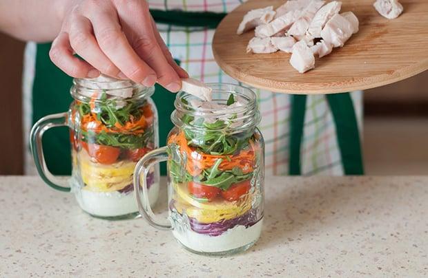 нарезанное запеченное куриное филе выкладывается в баночки с нарезанными овощами, фруктами, йогуртом и зеленью