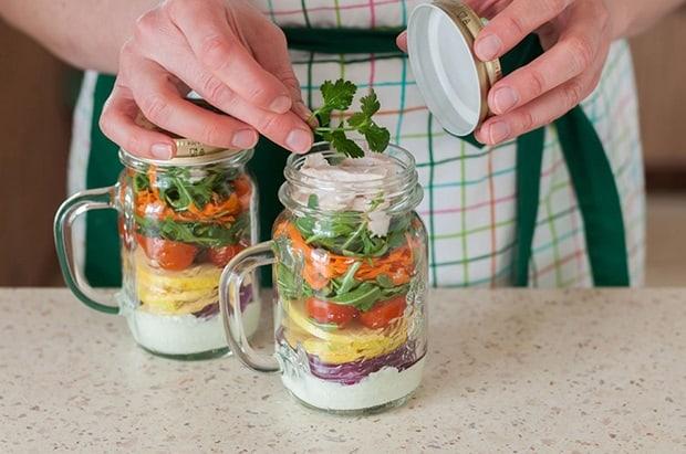 слоеный салат радуга с рукколой и овощами в двух баночках с ручками на столе