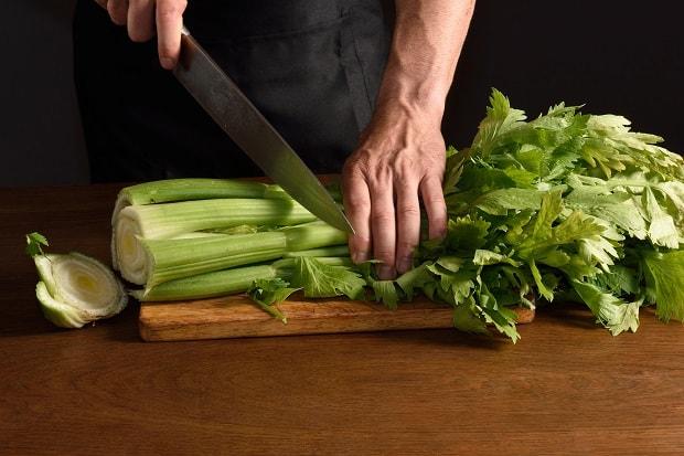 пучок стеблей сельдерея с листьями нарезается ножом на разделочной доске