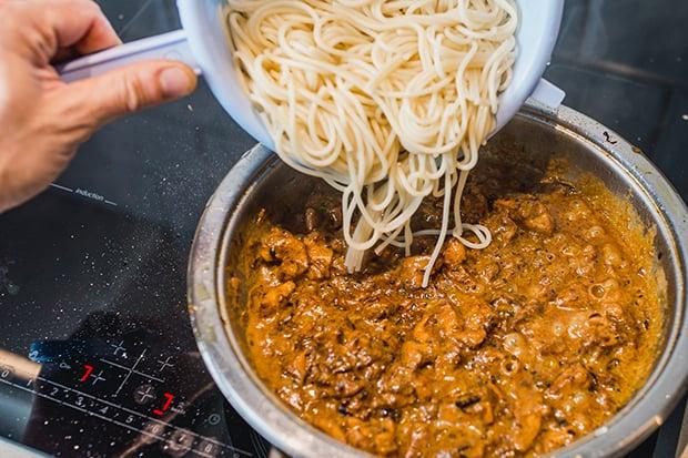 отварные спагетти выкладываются в сковороду с соусом