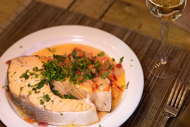 готовый стейк лосося с зеленью на тарелке