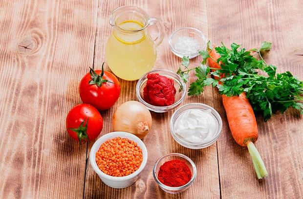 оранжевая чечевица, томатная паста, сметана и молотая паприка в соусниках, бульон в графине, два красных помидора, луковица, морковь, пучок петрушки