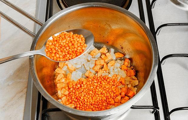 оранжевая чечевица добавляется в сотейник с нарезанными луком и морковкой