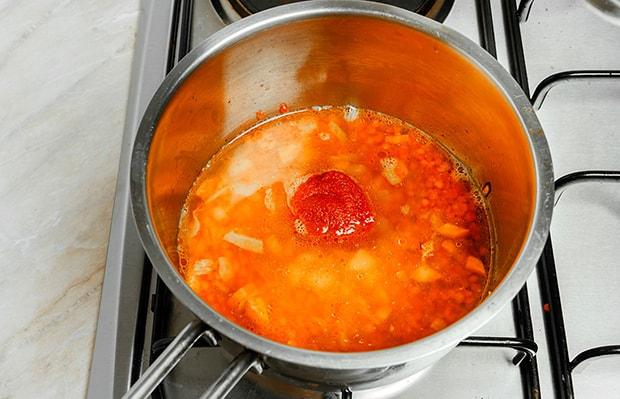 порция томатной пасты в сотейнике с бульоном и чечевицей на плите