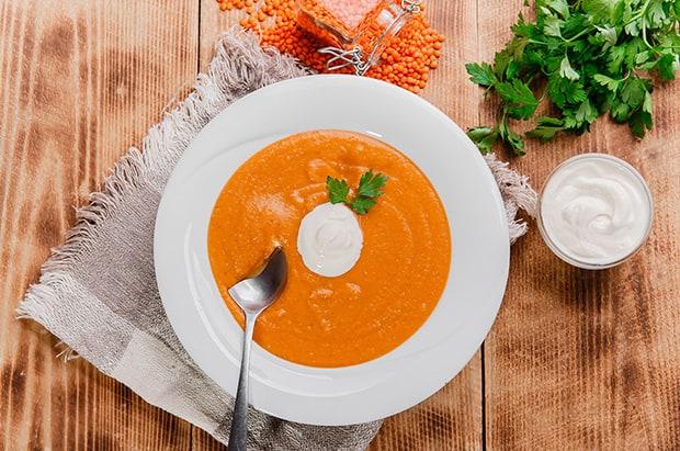 готовый суп-пюре из чечевицы с веточкой петрушки, порцией сметаны и ложкой в белой тарелке, рядом соусник со сметаной, оранжевая чечевица и пучок зелени