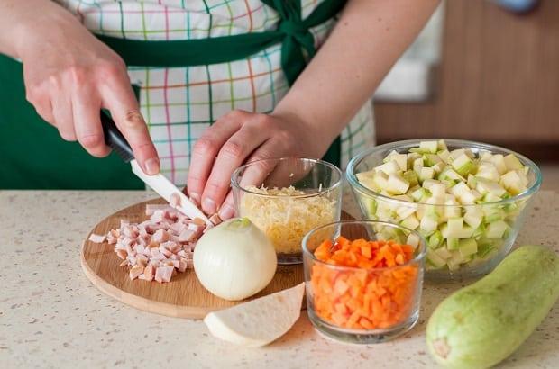 нарезанная кубиками ветчина и целая луковица на разделочной доске, тертый сыр, нарезанные кабачки и морковь в пиалах, свежий кабачок на столе