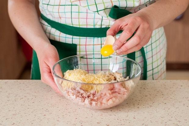 в миску с нарезанной ветчиной и тертым сыром добавляется яичный желток