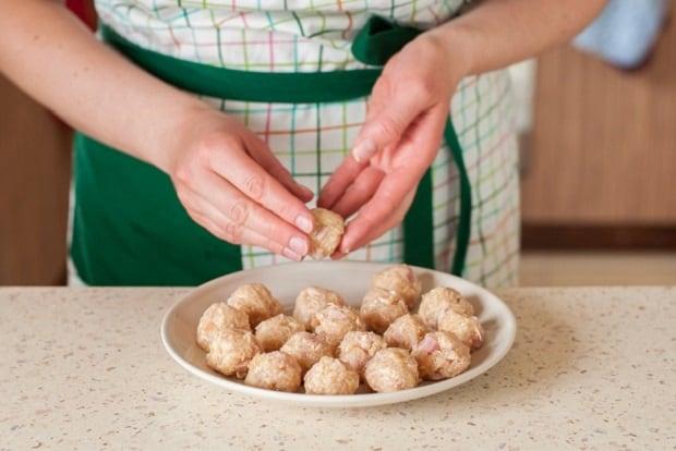 сырые куриные тефтельки на плоской тарелке на столе