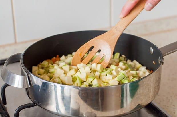 нарезанные кубиками кабачки в сковороде с лопаткой на плите