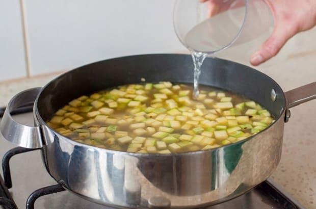 вода вливается в сковороду с обжаренными нарезанными кабачками