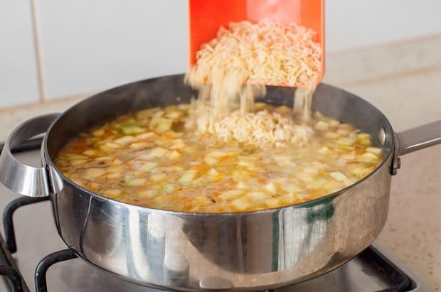 вермишель всыпается в сковороду с водой и обжаренными кабачками
