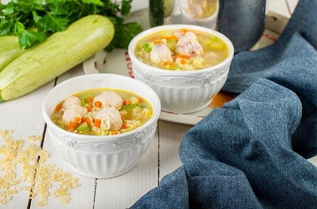 суп с тефтелями и овощами в двух пиалах, рядом скатерть и свежий кабачок