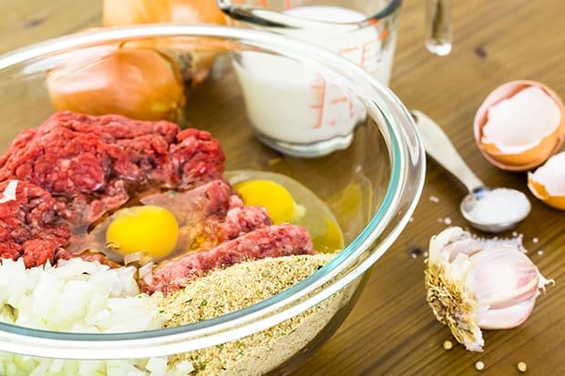 фарш с панировочными сухарями, яйцами и луком в миске