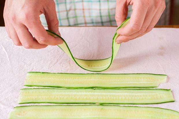 тонкие и длинные слайсы огурцов на столе, застеленном бумажной салфеткой