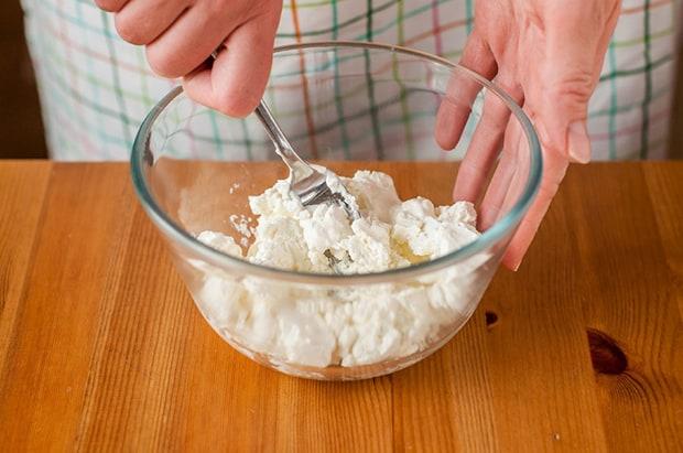 сыр фета разминается вилкой в прозрачной миске на столе