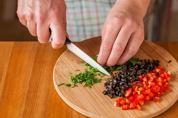 нарезанные кубиками маслины и красный перец на разделочной доске, рядом измельчается ножом петрушка