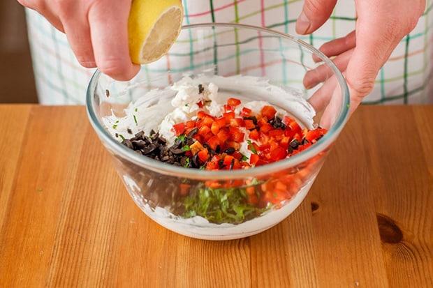надрезанный лимон выдавливается в миску с нарезанными маслинами, красным перцем, зеленью и сыром