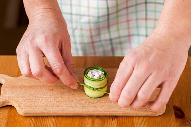 огуречный рулетик с сыром, перевязанный стеблем петрушки, на разделочной доске на столе