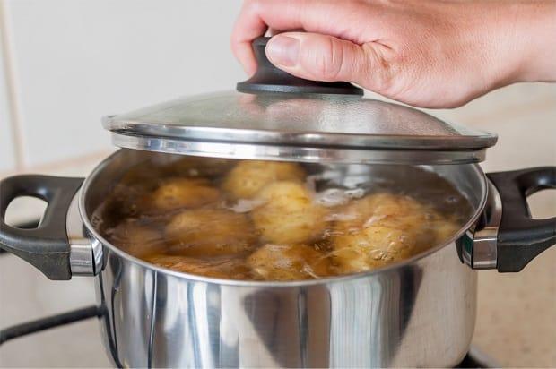 неочищенный картофель в кипящей воде в кастрюле на плите