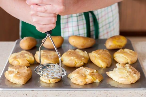 раздавленные вареные картофелины в мундирах на подставке