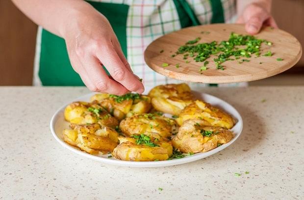 запеченный вареный картофель в мундирах посыпается нарезанным зеленым луком
