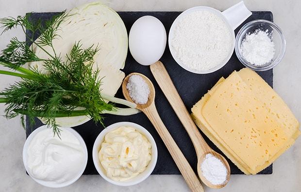 ломтики твердого сыра, сметана и майонез в соусниках, яйцо, половинка кочана капусты, соль, разрыхлитель в ложках