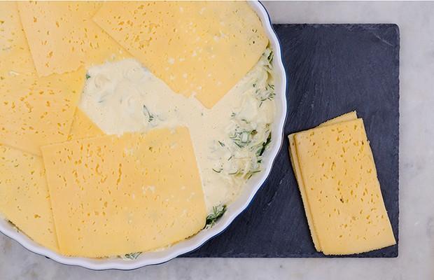 капуста с зеленью, залитая яичным кляром и покрытая ломтиками сыра в форме для запекания, рядом кусочки твердого сыра