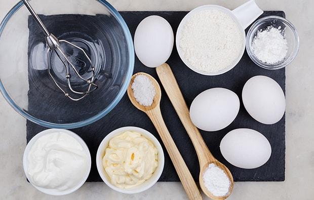 прозрачная миска с венчиком, яйца, сметана, майонез и мука в соусниках, соль и разрыхлитель в ложках