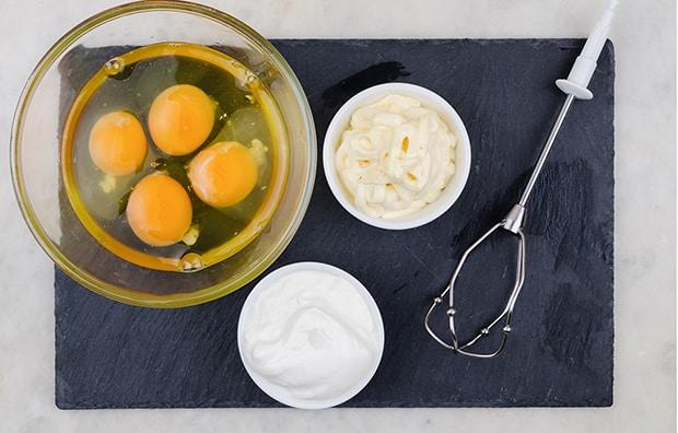 четыре разбитых яйца в прозрачной мисочке, рядом сметана и майонез в соусниках и венчик