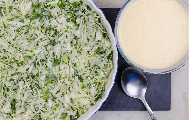 нашинкованная капуста с измельченной зеленью в миске, рядом яичный кляр в тарелке и ложка