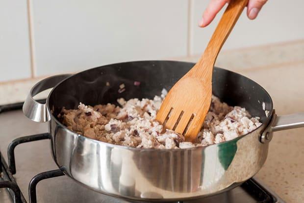 кусочки обжаренного куриного филе с деревянной лопаткой в сковороде на плите