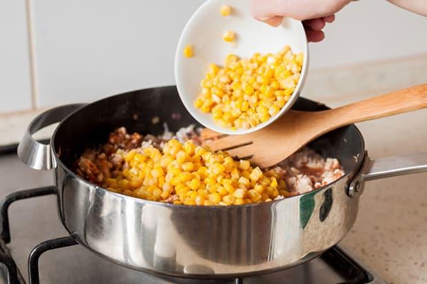 консервированная кукуруза добавляется в сковороду с кусочками куриного филе и лопаткой