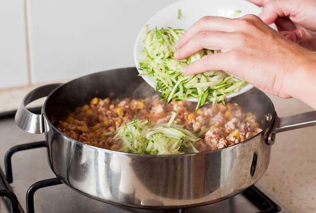 тертый свежий кабачок выкладывается в сковороду с обжаренным куриным филе и кукурузой