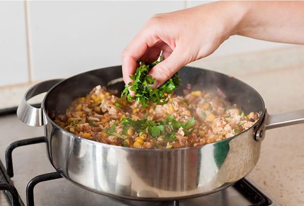 измельченная петрушка добавляется в сковороду с обжаренным куриным филе и кукурузой