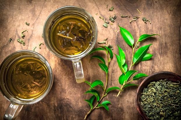 две кружки чая, сушеные листики в мисочке