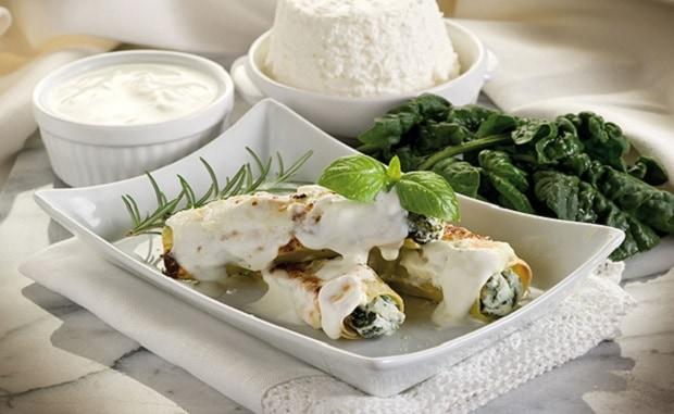 готовые каннеллони с рикоттой и шпинатом на тарелке со сметаной