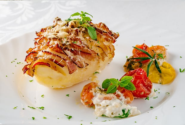 картошка-гармошка с беконом и овощами на тарелке