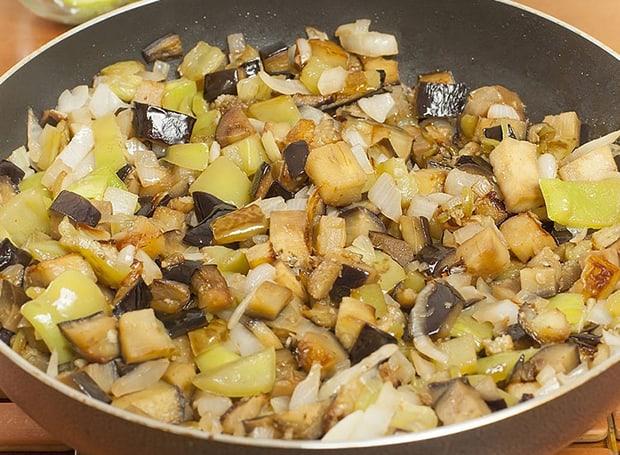 нарезанные баклажаны с перцем и луком на сковороде