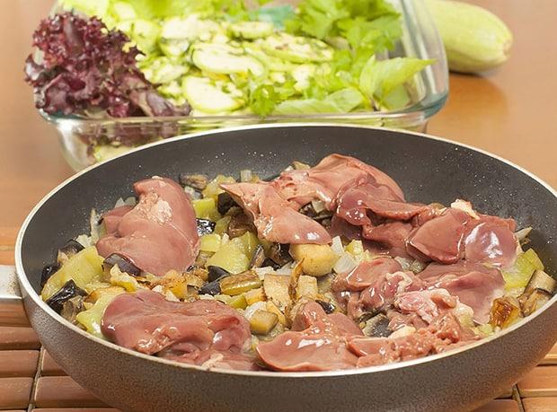свежая куриная печень с овощами на сковороде