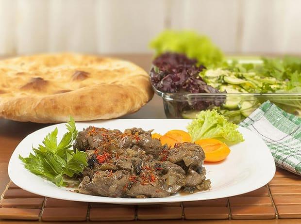 куриная печень с овощами и зеленью на тарелке, рядом лаваш