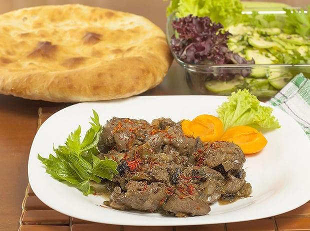 тушеная куриная печень с овощами на тарелке, лаваш и зелень