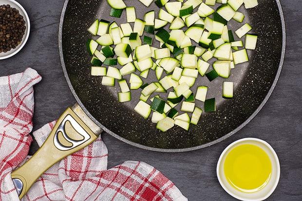 нарезанные кабачки в сковороде, масло в пиале